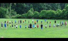On Tuesday evening, July 18, campers gathered in a circle on the practice field for stretching and warm-up exercises.