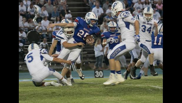 A-J seniors Gavin Tripp, number 17 in white uniform, and Cameron Tweedy, number 5, tackle a Nashville ball carrier. Also in the photo are A-J players Wyatt Johnson, number 9, a senior, and Derek Nelson, number 34, a junior