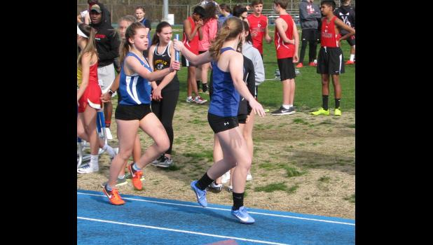 Julia Hall handed the baton to Julia Ellis during a leg in the 4 x 800 meter relay event.