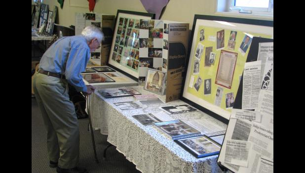 Norman Hickam, who is the oldest member of the church, viewed some of the items which were on display last Saturday evening.
