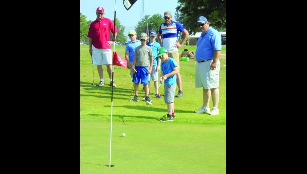 Campers and coaches watch to see if the ball will roll into the hole. The golfers were competing in a golf scramble on June 20, the final day of a junior golf program at the Union County Country Club in Anna. Photo and story by Amber Skelton.