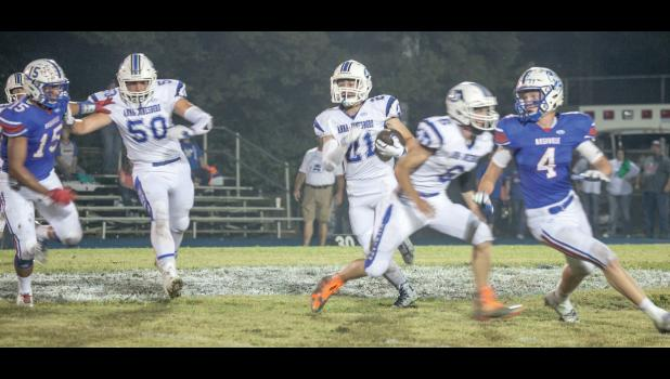 A-J's Dylan Fox, number 21, looks for some running room. Austin Dillow, number 50, and Caleb Clover, number 6, are blocking for the A-J runner.