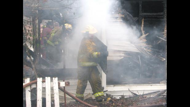 A firefighter removes debris from a house in Anna Monday morning.