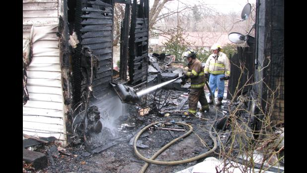 Water is sprayed on smoldering remains at a house fire in Anna Monday morning.