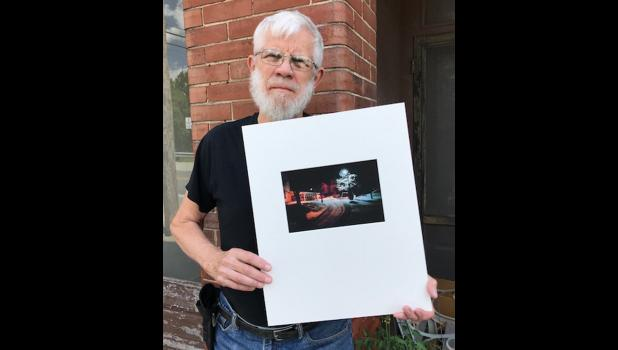 """Charles Swedlund holds one of his """"Cobden at Night"""" photographs. The Union County Historical and Genealogy Society plans to present an exhibit featuring the photographs during the Cobden Peach Festival. Photo provided."""