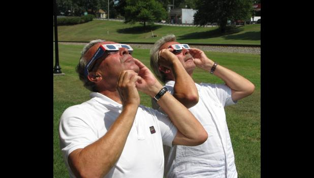 Niels Moeller, left, and Karsten Moeller, both of Copenhagen, Denmark, watched the total solar eclipse Monday in downtown Cobden. They were wearing protective eyeglasses while watching the eclipse.