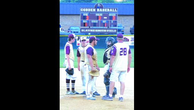 Cobden coach Dana Pearson confers with his players during the third inning of Monday night's game.
