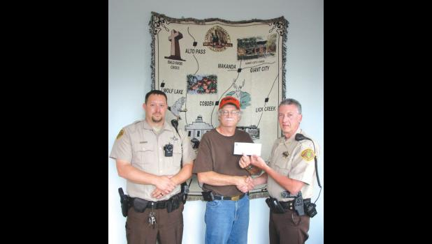 Whitetails Unlimited Union County chapter chairperson Wes Burris, center, presented a  check to Union County Sheriff Scott Harvel, right, to help support the sheriff's office's plans to acquire a new K-9 police dog. Union County Sheriff's Office Deputy Eric Ralls will be handling the K-9 police dog.