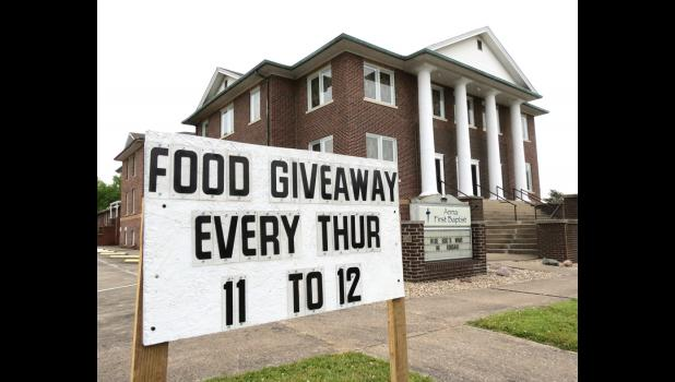 A sign notes that a food giveaway is planned on Thursdays at the First Baptist Church in Anna.
