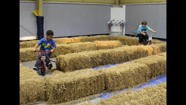 Haystack maze: Tydell Gathright and Wayne Peach rode tricycles through the haystack maze.