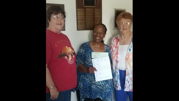 From left are Margaret Ann Grace; Jeanine Woods, a Cairo Women's Shelter representative; and June Badgley. They are shown presenting and receiving the $200 grant.