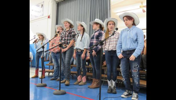 The junior high choir looked the part in cowboy hats, boots and flannel. They sang and performed a dance for the audience. Photo by Amber Skelton.