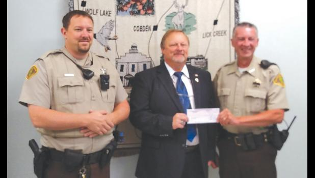 Kevin Starr, center, presented a donation to Sheriff Scott Harvel, right, for the sheriff's office's K-9 fund. Deputy Eric Ralls, left, was also present. Photo provided.
