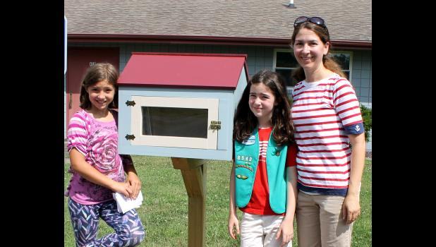 Girl Scouts Adrianna Smothers, Lillian Belmont and troop leader Emily Taylor spent the day promoting the new Little Free Library and passing out Girl Scout cookies. Photo by Lindsey Rae Vaughn.