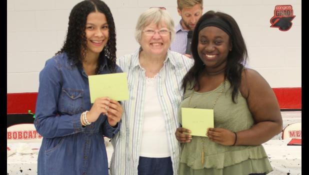 Pulaski-Alexander Illinois Association of Home and Community Education member Ledillon Powers, center, presented Kira Davis, left, and Gabriele Baker, right, their $500 scholarships at the Meridian High School senior awards banquet.