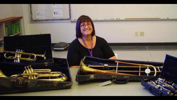 Teacher Rebecca Yates sits with some of the worn and weathered instruments that have been found in Century School's storage. A donation fund has been set up to raise money for new instruments that can be loaned out for student use. Photo by Amber Skelton.