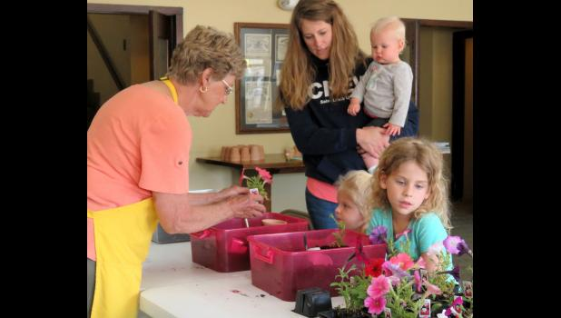 Anna-Jo Garden Club member Linda Karraker helped Maeve and Mia Kell pick out flowers for the pots they had painted during an annual Paint and Plant program Friday afternoon, May 12, at Stinson Memorial Library in Anna. Photo by Amber Skelton.