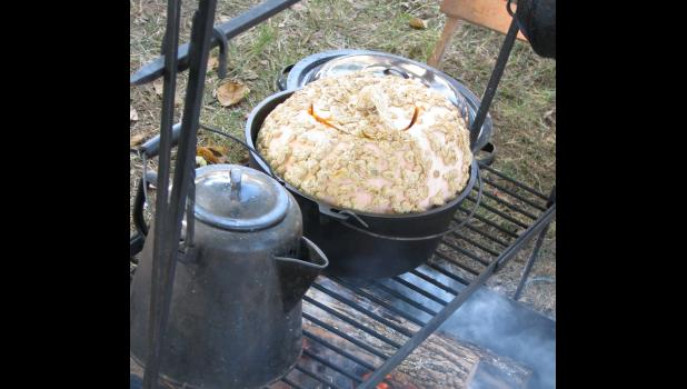 A pumpkin was baking in a Dutch oven over a cook fire. The pumpkin was filled with apples and brown sugar and butter and all sorts of others things which aren't any good for you.