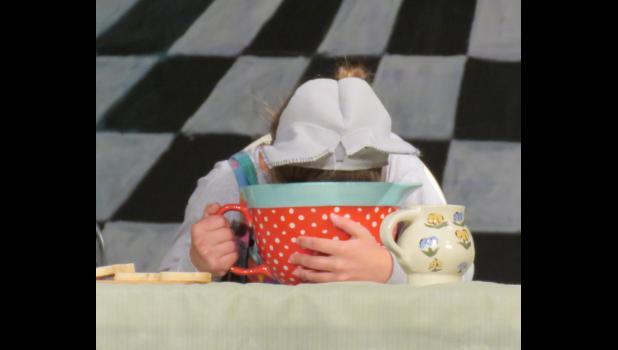 The Dormouse, played by Kenzie Stover, fell asleep in her tea after telling a nursery rhyme.