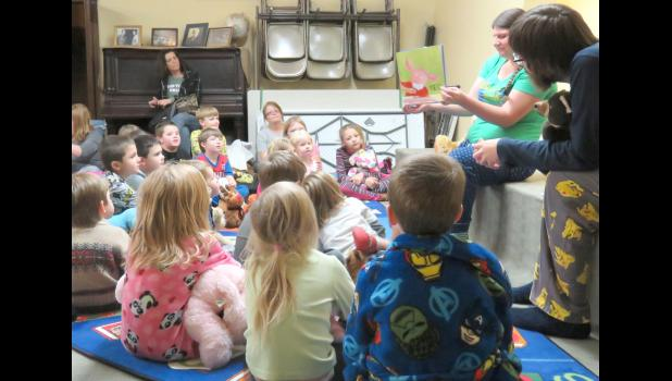 Children listened with their stuffed animals as  Stinson Memorial Library staff member Ms. Beth read them a bedtime story. Photo by Amber Skelton.