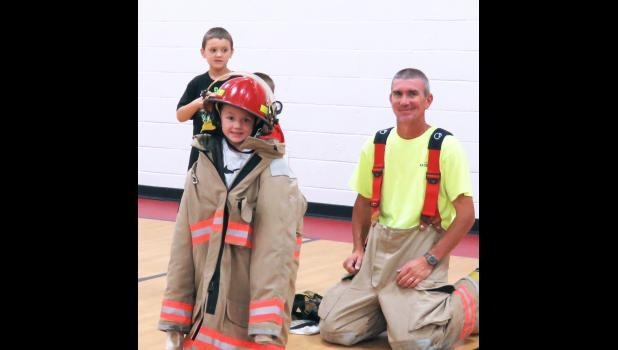 Firefighter TC Schaefer, right, helped Rusty Smith, center, to try on some firefighting gear during a visit to Shawnee Elementary School. Also in the picture is Kyle Shirley. Photo by Amber Skelton.