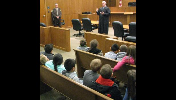 Union County Presiding Judge Mark Boie, standing at right, talked with Anna School District No. 37 students and their teachers Friday morning, Oct. 27. Union County Sheriff Scott Harvel, left, was leading the students on a tour of the Union County Courthouse in Jonesboro.