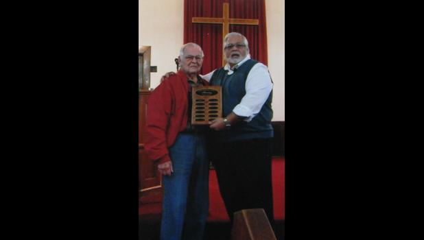 Dan Wilson, left, was presented with a plaque by the Rev. Carl Mesiti. Photo provided.