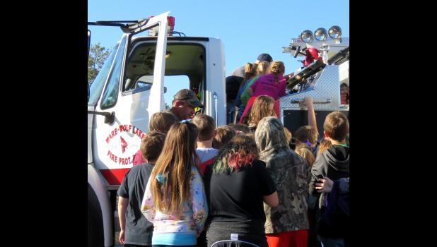 Students crowded around to explore the fleet of fire trucks in the Shawnee School parking lot Tuesday morning. Photo by Amber Skelton.