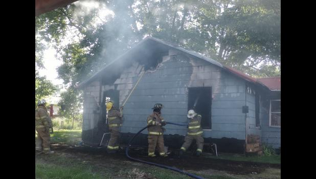 Firefighters from the Ware-Wolf Lake, Alto Pass, and Jonesboro Fire Departments hosed down what was left of a house in Wolf Lake after a fire caught Monday evening.